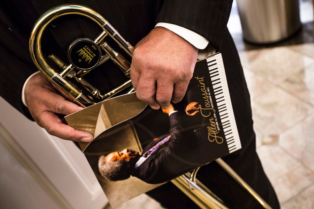 A musician holds his trombone as close as he does the Allen Toussaint memorial program book. 11/20/15 ©Zack Smith Photography