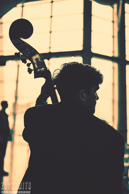 A Bass player for the Tulane Marching Band is silhouetted at the WWII Museum.