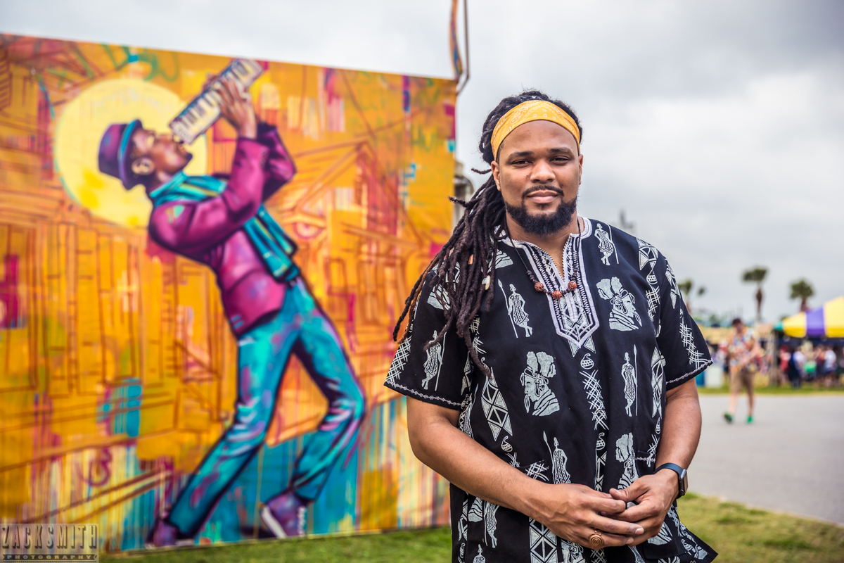 New Orleans muralist and poster artist BMike, Brandon Odums,  poses in front of his original painting of New Orleans musician Jonathan Batiste.